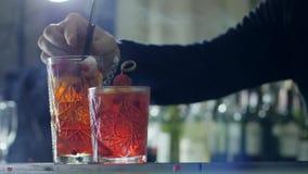 Het wapen van de mens neemt zwart stro in het verfrissen van drank met ijs en bessen op barteller in op gemakkelijke nevel stock videobeelden