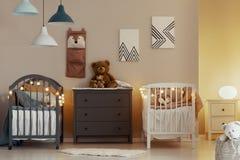 Het warme binnenland van de babyslaapkamer met witte en grijze voederbakken, ladenkast en kleine nightstandlijst met lamp stock afbeeldingen