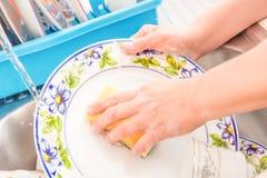 Het wassen van de schotels op de keukengootsteen Stock Foto