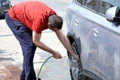 Het wassen van een auto van een slang Stock Fotografie