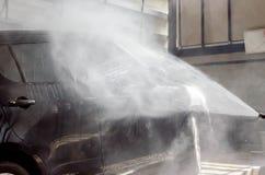 Het wassen van zwarte auto door het kanon van de drukwasmachine in autowasserettewinkel Stock Foto