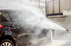 Het wassen van zwarte auto door het kanon van de drukwasmachine in autowasserettewinkel Stock Afbeelding