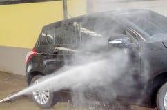 Het wassen van zwarte auto door het kanon van de drukwasmachine in autowasserettewinkel Stock Afbeeldingen