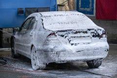 Het wassen van zwarte auto met actief schuim De mens wast schuimmachine Schone machine, autowasserette met spons en slang stock fotografie
