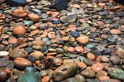 Het water is daling aan kleurrijke rots in middagtijd royalty-vrije stock afbeelding