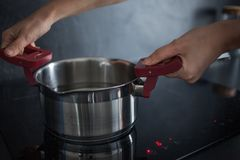 Het water in de pan is op de inductiehaardplaat Thuis het koken royalty-vrije stock foto's