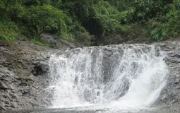 Het water die tussen rotsen in een rivier vallen is een natuurlijk landschap in de provincies van de Filippijnen stock foto's