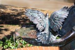 Het water die van metaalkom stromen met gehouden door handen van standbeeld met metaalvogels streek met uitgespreide vleugels nee stock afbeelding