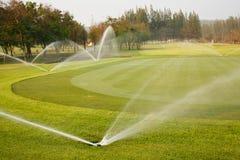 Het water geven in golfcursus Stock Foto's