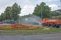 Het water geven van het bloembed bij een rotonde royalty-vrije stock afbeeldingen
