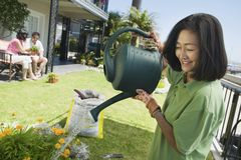 Het water geven van de vrouw installaties in tuin Stock Afbeelding
