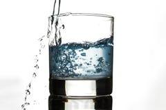 Het water giet door het glas op een witte achtergrond royalty-vrije stock afbeelding