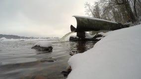 Het water giet van de afval-pijp in de rivier in de winter stock footage