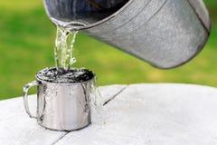 Het water giet van de emmer uit in de mok stock foto