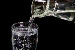 Het water giet van een glaskruik in een glas Stock Foto