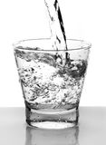 Het water goot in glas Royalty-vrije Stock Afbeeldingen