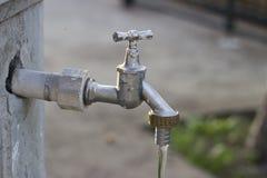 Het water komt uit uit de Tapkraan Stock Afbeeldingen