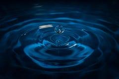 Het water laat vallen golven met blauwe achtergrond en bezinning royalty-vrije stock fotografie
