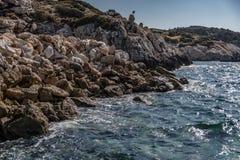 Het water slaat op de rotsen van de kust in Griekenland stock foto