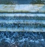Het water stroomt onderaan marmeren stappen Stock Foto