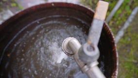 Het water van de kraan giet in een groot oud roestig vat vullend het Rust in het land De inzameling van water stock videobeelden