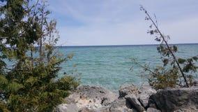 Het water van het Mackinaceiland met bomen en rotsen stock fotografie