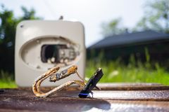 Het water het verwarmen element van corrosie wordt beschadigd ligt op een houten lijst naast de boiler die In het groene gras als royalty-vrije stock foto