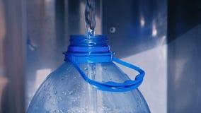 Het water wordt gegoten in een plastic fles stock footage