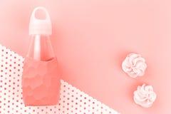 Het waterfles en koekjes van de koraalkleur op stipkoraal royalty-vrije stock foto's