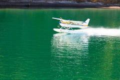 Het watervliegtuig dat van vliegtuigen op kalm water van meer opstijgt Royalty-vrije Stock Afbeelding