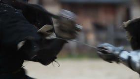 Het weer invoeren van middeleeuwse toernooien Twee sterke strijdersridders die bij arena vechten stock videobeelden