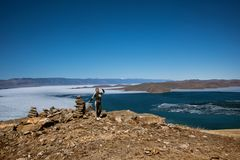 Het Weergeven boven groot mooi meer Baikal met Ijsijsschollen die op het water en het meisje drijven bevindt zich dichtbij rotsen royalty-vrije stock afbeelding