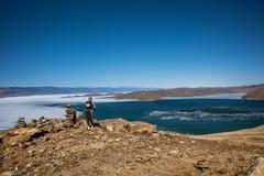 Het Weergeven boven groot mooi meer Baikal met Ijsijsschollen die op het water en het meisje drijven bevindt zich dichtbij rotsen royalty-vrije stock foto