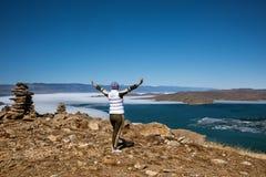 Het Weergeven boven groot mooi meer Baikal met Ijsijsschollen die op het water en het meisje drijven bevindt zich dichtbij rotsen stock fotografie