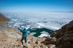 Het Weergeven boven groot mooi meer Baikal met Ijsijsschollen die op het water met meisje drijven draagt matroos, Rusland stock afbeeldingen