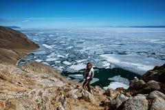 Het Weergeven boven groot mooi meer Baikal met Ijsijsschollen die op het water met meisje drijven draagt wit jasje, Rusland royalty-vrije stock afbeeldingen