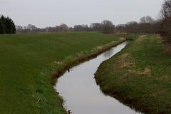 Het Weergeven op graaft gevuld die met water door een grasgebied wordt omringd in rhede emsland Duitsland royalty-vrije stock afbeeldingen