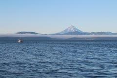 Het Weergeven van de Vilyuchinsky-vulkaan riep ook Vilyuchik van toeristenboot De wolk ligt op de kustklippen royalty-vrije stock afbeelding