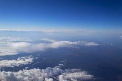 Het Weergeven van het venster van het vliegtuig aan de cumulus betrekt en de oneindig blauwe hemel royalty-vrije stock foto's