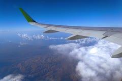 Het Weergeven van het venster van het vliegtuig aan de cumulus betrekt en de oneindig blauwe hemel stock foto's