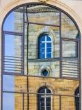 Het weerspiegelen van een oud huis in venster stock afbeelding