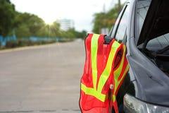 Het weerspiegelende vest van de netwerkveiligheid met gebroken auto op de weg royalty-vrije stock foto