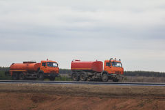 Het wegenbouwwerk - twee rode het water geven vrachtwagens bij weg onder gebied Stock Fotografie