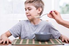 Het weigeren om doend walgen voedsel te eten stock foto