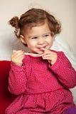 Het weinig vrij leuke meisje eet Kerstmissnoepjes stock fotografie