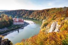 Het Weltenburgklooster en Donaudurchbruch bij de rivier van Donau in Beieren, Duitsland omringden door de oranje gekleurde herfst Stock Foto's