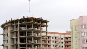 Het werk aangaande de bouwwerf De bouwers werken aan de bovenkant van de bouw van beton stock videobeelden