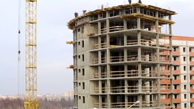 Het werk aangaande de bouwwerf De bouwers werken aan de bovenkant van de bouw van beton stock footage