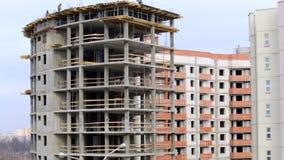 Het werk aangaande de bouwwerf De bouwers werken aan de bovenkant van de bouw van beton stock video