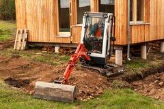 Het werk aangaande de bouwwerf van een ecologisch huis Het graafwerktuig past het terrein aan Een kleine graver in de tuin Royalty-vrije Stock Foto's